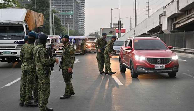 Philippine police personnel man a checkpoint bordering nearby Cavite province and suburban Las Pinas