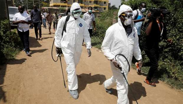 Kenyan health workers dressed in protective suits walk after disinfecting the residence where a coro