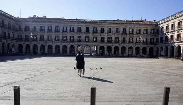 A woman crosses a virtually deserted square, amidst concerns over Spain's coronavirus outbreak, in t