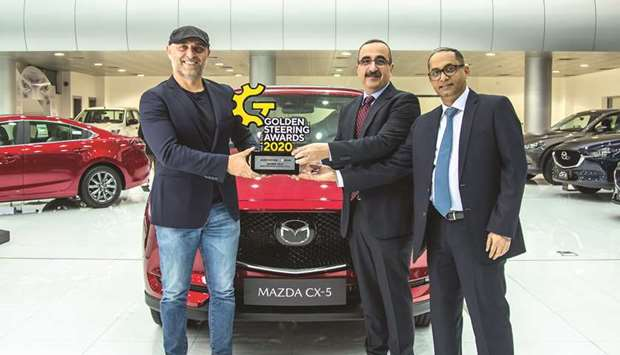 Officials pose with the award in front of the Mazda CX-5.