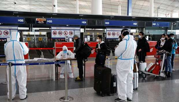 Staff members wearing protective suits register passengers in front of a check-in counter of Air Chi