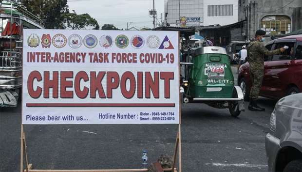 Checkpoint signage is seen as a soldier (R) checks the temperature of a motorist before entering Man