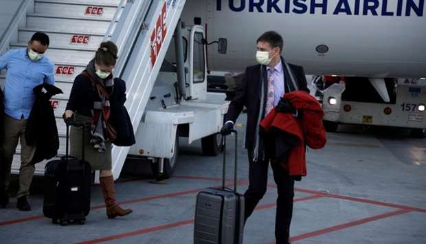 A passenger wears a protective face mask in light of the coronavirus, upon arrival at Istanbul Airpo