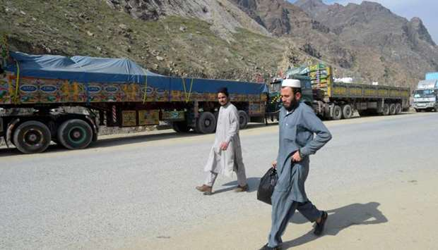 Men walk past Afghan's trucks parked along a road near the closed Pakistan-Afghanistan border amid c