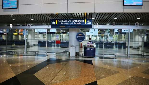 An airport care ambassador wearing protective mask, waits for passengers at the empty international