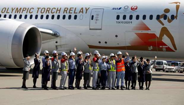 Staff members of Japan Airlines and All Nippon Airways and runway crew wave as they see off the 'Tok