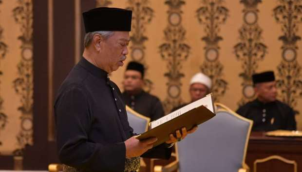 Malaysia's incoming Prime Minister Muhyiddin Yassin reading the oath during his swearing-in ceremony