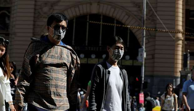 People wearing face masks walk by Flinders Street Station after cases of the coronavirus were confir