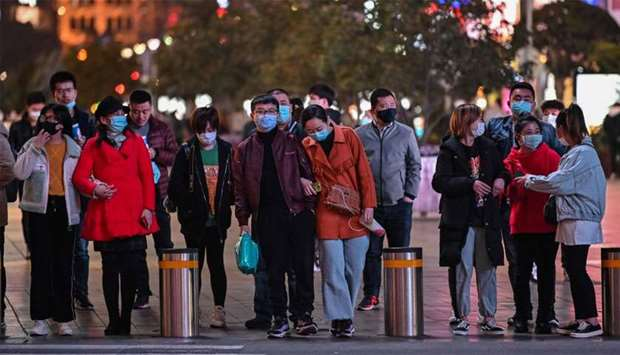 People wearing face masks amid concerns over the COVID-19 coronavirus outbreak walk in Shanghai