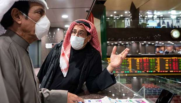 Kuwaiti traders wear face masks, following the outbreak of the new coronavirus, as they stand on the