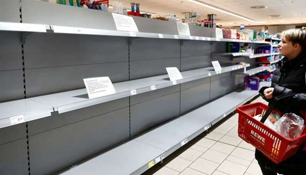 A woman looks at an empty shelf with a sign announcing the rationing at a grocery store