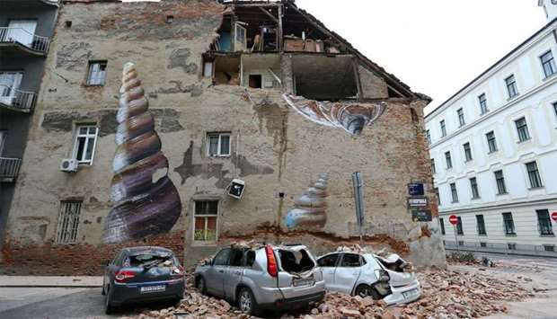 Damaged cars and a partially damaged building are seen following an earthquake, in Zagreb, Croatia
