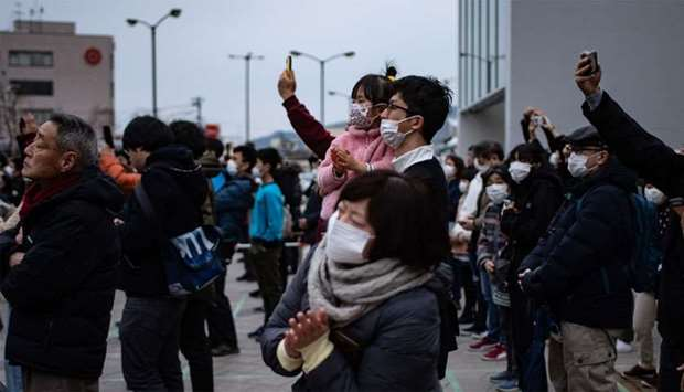 People wearing face masks watch the Tokyo 2020 Olympic flame displayed outside Miyako railway statio