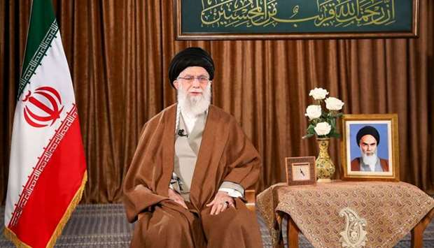 Iran's Supreme Leader Ayatollah Ali Khamenei delivering a speech, with a portrait of the late founde