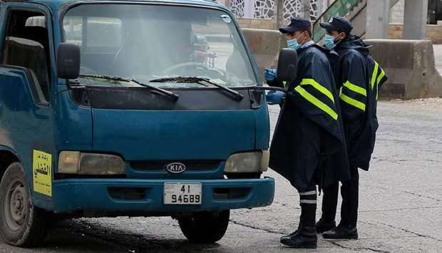Police officers manning a checkpoint speak to a truck driver in the capital Amman during a nationwid