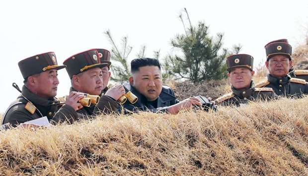 North Korean leader Kim Jong-un (centre) inspecting an artillery fire competition between large comb
