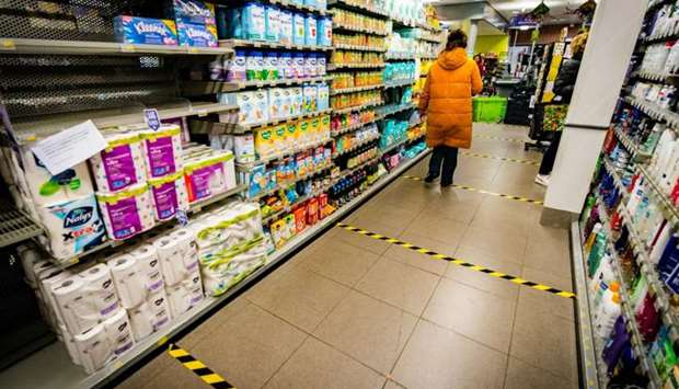 A customer walks in a supermarket with security distance marks on the floor in Engelen as a measure