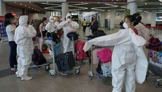 A group of travelers wear full protective suits and masks at Phnom Penh International Airport in Cam
