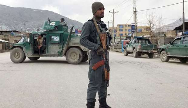 An Afghan policeman stands guard near the site of an attack in Kabul, Afghanistan