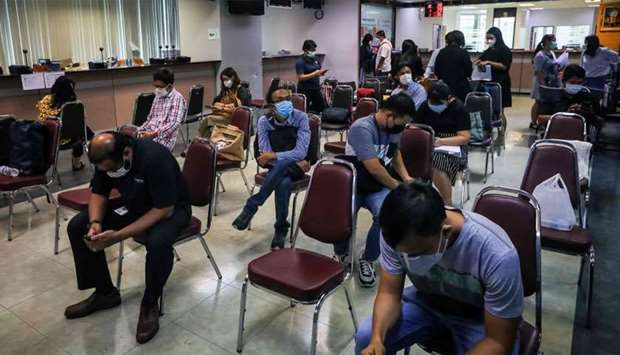 People sit apart from each other to maintain social distancing at an immigration office in Bangkok