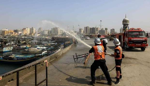 Members of the Palestinian civil defense force spray disinfectant in the port area in Gaza City, dur