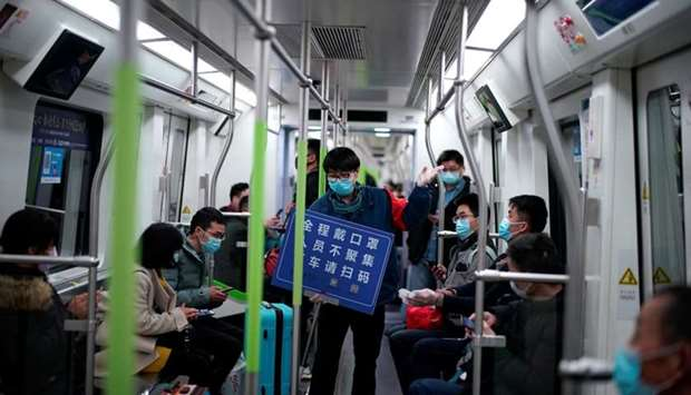 A staff member wearing a face mask holds a placard while standing among passengers on a subway train
