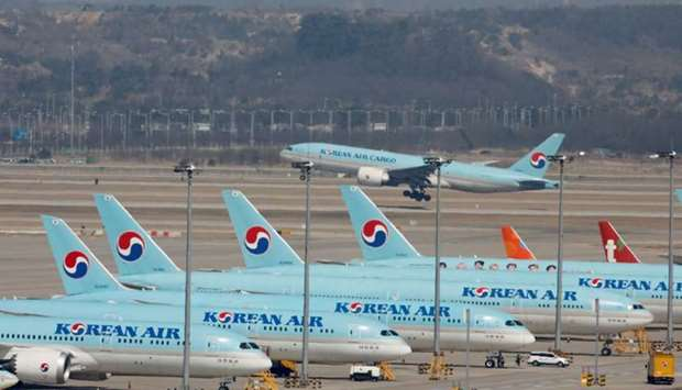 Korean Air's passenger planes are parked on the tarmac as overseas flight routes are reduced followi