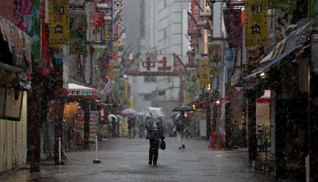 A man walks past on a nearly empty street in a snow fall during the first weekend after Tokyo Govern