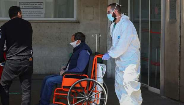 A healthcare worker wearing a protective face mask and suit pushes a patient in a wheelchair near th