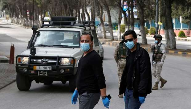 People wear face masks at a check point in the northern governorate of Irbid, Jordan, as the city ha