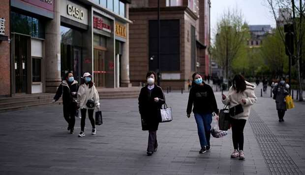 People wearing face masks walk at a shopping area in Wuhan, Hubei province, the epicentre of China's