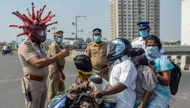 Police inspector Rajesh Babu wearing a coronavirus-themed helmet speaks to a family on a motorbike a