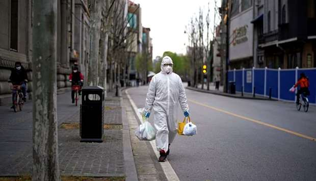 A man wearing a hazmat suit walks on a street in Wuhan, Hubei province, the epicenter of China's cor