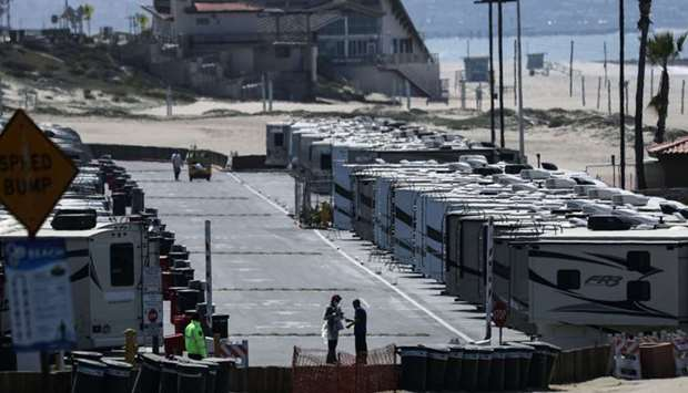 People stand near RV's at Dockweiler State Beach, in an area being used as an isolation zone for tho