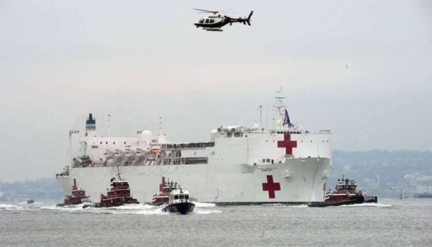 The USNS Comfort medical ship moves up the Hudson River past the Statue of Liberty as it arrives in