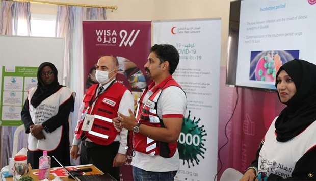 Officials of Qatar Manpower Solutions Company (WISA), and the Qatar Red Crescent Society making a pr