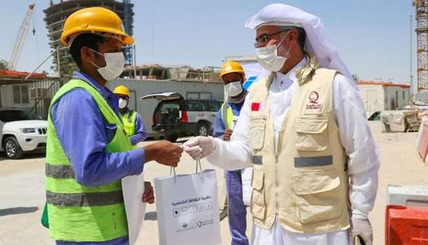A Qatar Charity official handing over a kit to a worker.