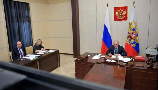 Russian President Vladimir Putin and Finance Minister Anton Siluanov take part in a video link, held