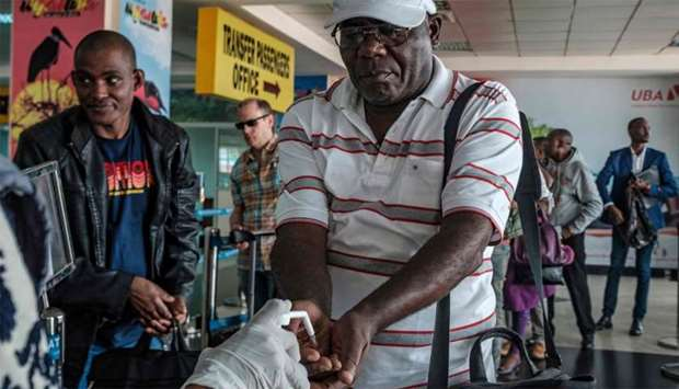 Passengers arriving on international flights are asked to desinfect their hands at Entebbe Airport a