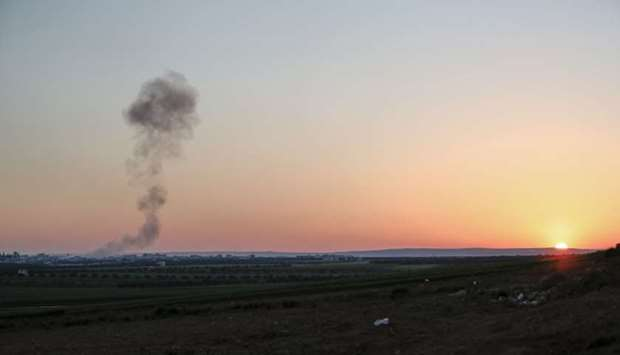 Smoke billows above the rebel-controlled village of Sarmin near the regime-held town of Saraqeb, in