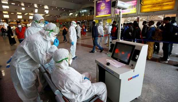 Medical staff in protective gear look at a screen while checking temperatures of passengers upon the