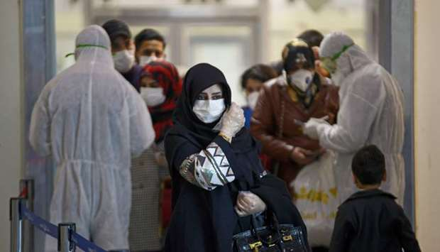 Medical staff in protective gears distribute information sheets to Iraqi passengers returning from I