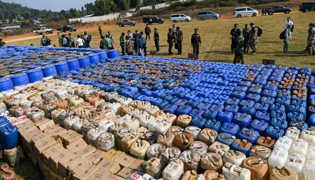 Foreign military attachés check drugs in a football ground where seized drugs, vehicles, laboratory