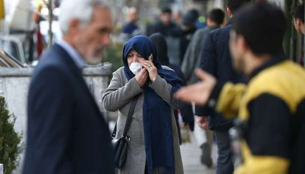 An Iranian woman wears a protective face mask, following the coronavirus outbreak, as she talks on t