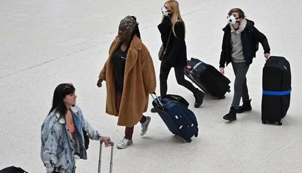 Travellers wearing protective face masks pull their suitcases while walking across the concourse at