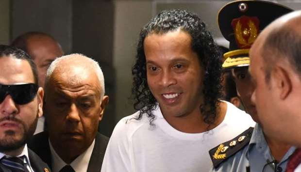 Brazilian retired football player Ronaldinho (C) arrives at Asuncion's Justice Palace