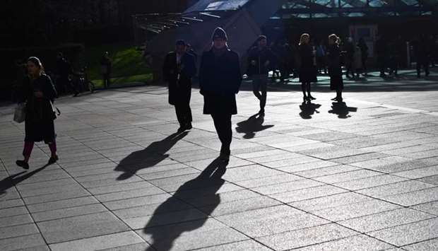 Commuters walk through Canary Wharf, as the number of coronavirus cases grow around the world and as