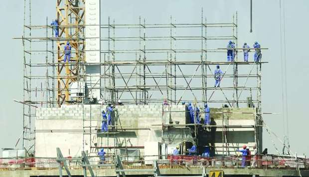 Labourers installing scaffolding at the construction site of a new building in Doha (file).