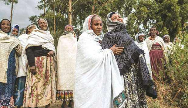 People mourn the victims of a massacre allegedly perpetrated by Eritrean soldiers in the village of