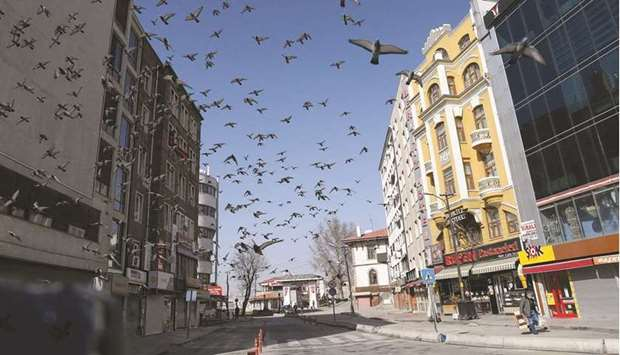 Birds fly past a solitary pedestrian in Ulus District of Ankara during a weekend curfew imposed by a